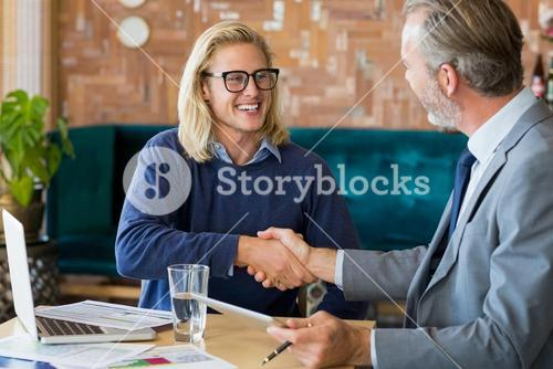 Business colleagues shaking hands in meeting
