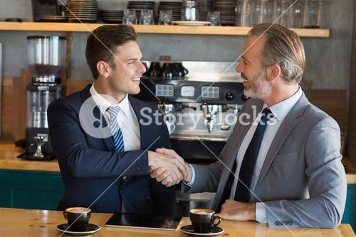 Businessmen shaking hands in café