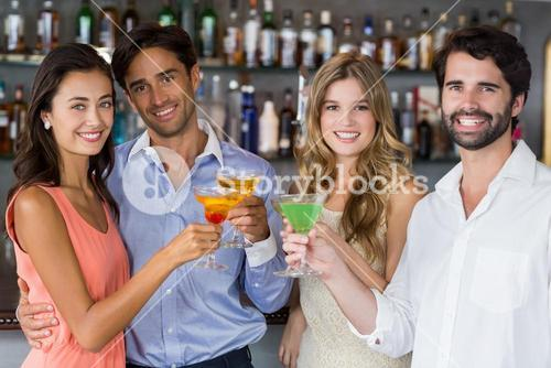 Portrait of happy couples toasting cocktail glasses