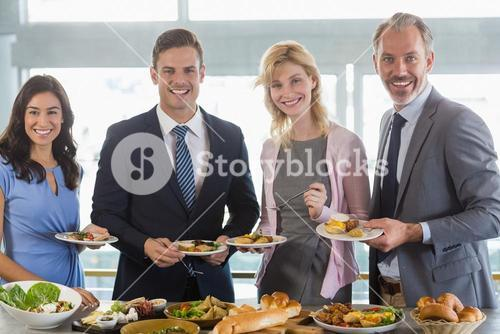 Portrait of business colleagues serving themselves at buffet lunch