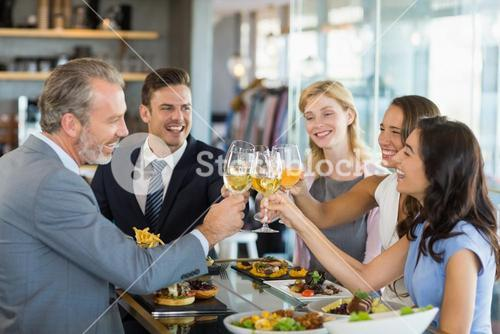 Happy business colleagues toasting beer glasses while having lunch
