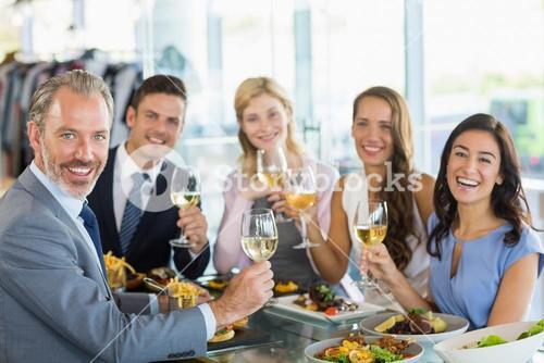 Portrait of happy business colleagues toasting beer glasses while having lunch