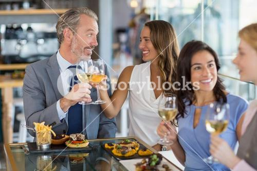 Happy business colleagues interacting and toasting beer glasses while having lunch