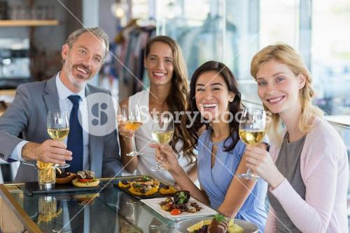 Portrait of happy business colleagues holding beer glasses while having lunch