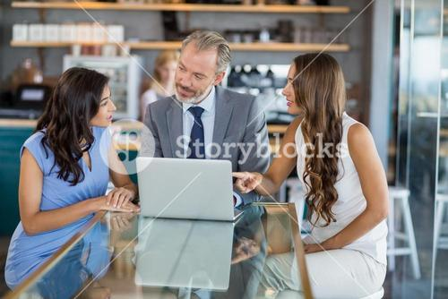 Business colleagues discussing over a laptop