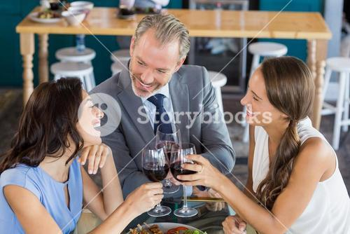 Happy business colleagues toasting wine glass