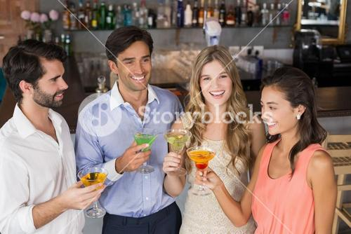 Happy friends holding cocktail glasses