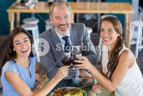 Businessman and colleague toasting glasses of wine in restaurant