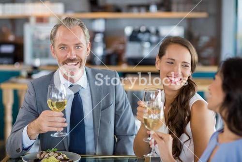 Businessman smiling at camera while colleague toasting glasses of wine