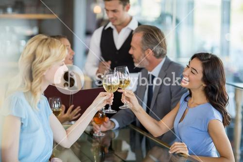 Waiter taking the order while colleagues toasting glasses of wine
