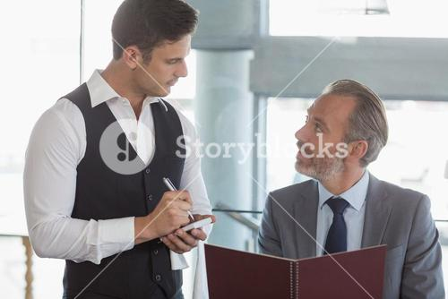 Waiter taking the order from a businessman