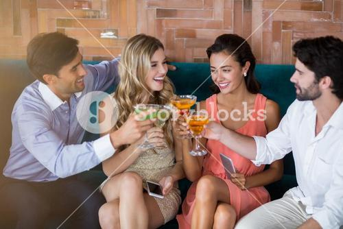 Group of friends toasting glasses of cocktail