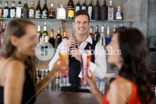 Two women having cocktail while a waiter preparing cocktail with cocktail shaker