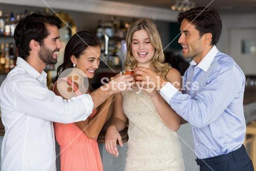 Group of friends toasting  glasses of tequila shot