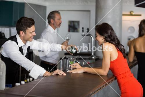Waiter pouring cocktail into cocktail glass
