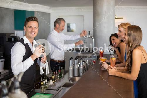 Beautiful women having cocktail while waiter preparing cocktail with cocktail shaker