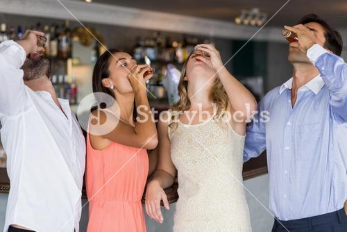 Group of friends having tequila shot