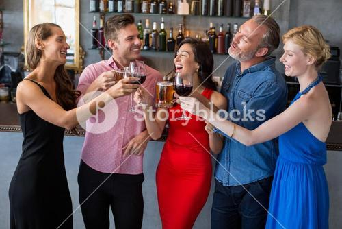 Group of friends toasting glasses of beer and wine