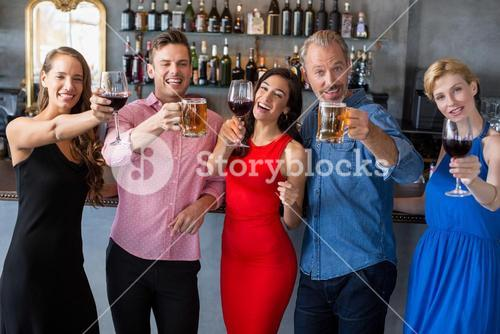 Group of friends holding glasses of beer and wine