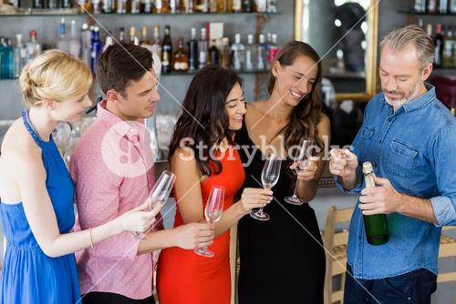 Friends looking man to open the champagne bottle