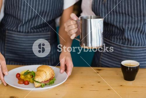 Mid section of two waitresses holding plate of meal and coffee jug