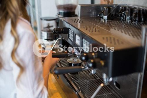 Mid section of waitress making cup of coffee