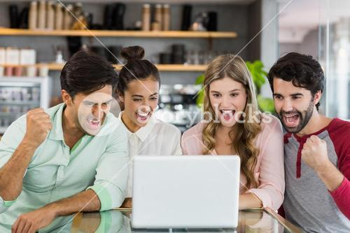 Group of excited friends using laptop