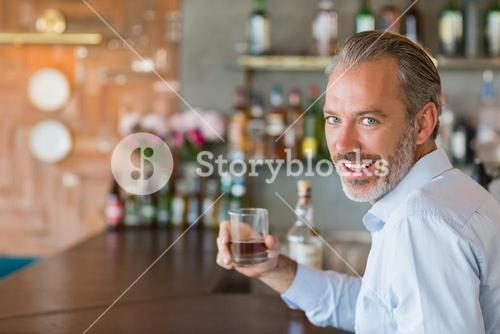 Portrait of man holding glass of whiskey