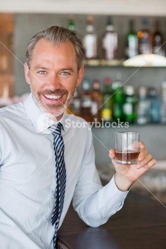 Happy man holding a glass of whiskey