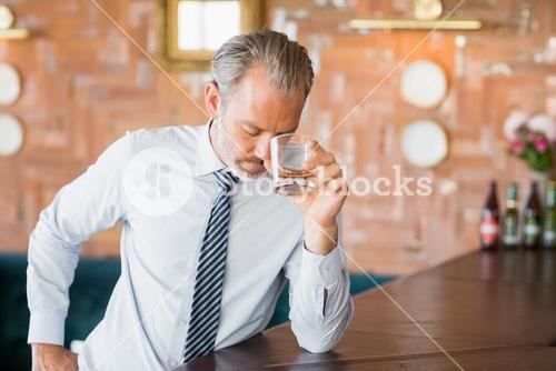 Businessman clutching whiskey glass to forehead
