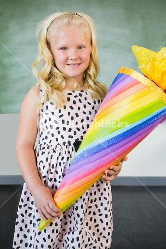 Portrait of smiling schoolgirl holding gift in classroom
