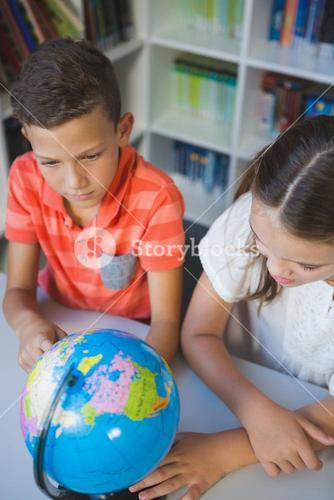School kids studying globe in library