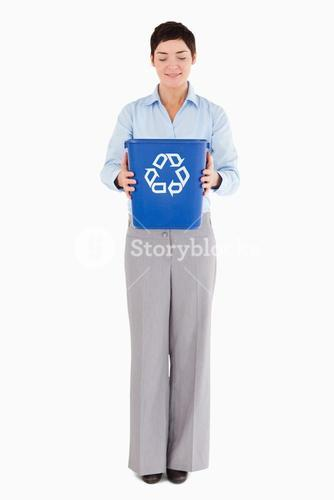 Businesswoman holding a recycling bin