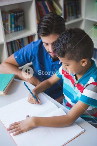 Teacher helping school kid with his homework in library
