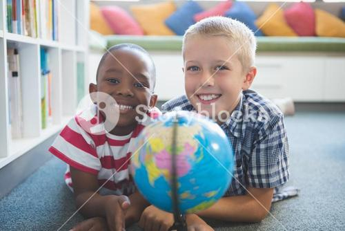 Portrait of school kids studying globe in library