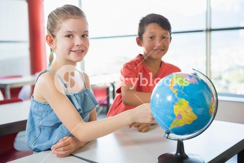 School kids studying globe in classroom