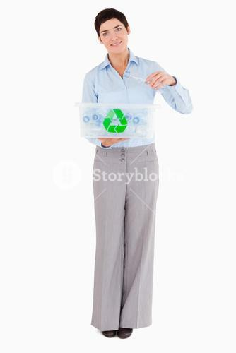 Woman putting a plastic bottle in a recycling box