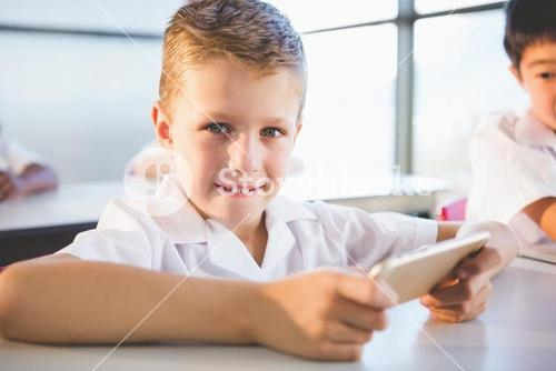 Schoolkid using mobile phone in classroom