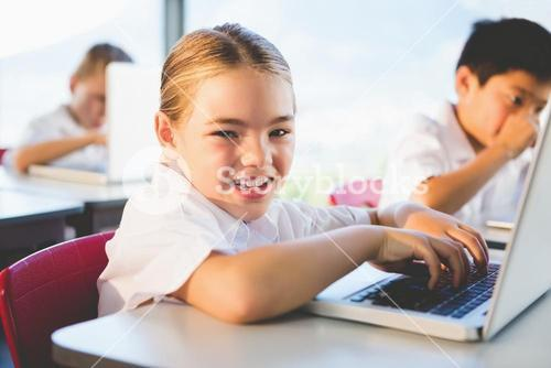 Schoolkids using laptop in classroom