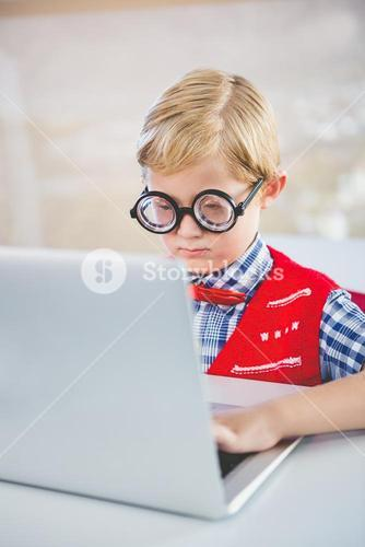 Close-up of schoolkid using laptop in classroom