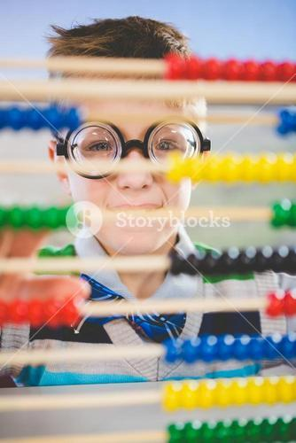 Close-up of schoolkid looking through abacus in classroom