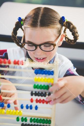 Close-up of schoolkid counting abacus in classroom