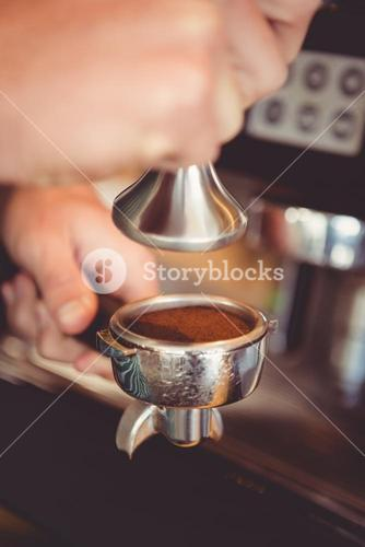 Hands holding tamper with coffee powder