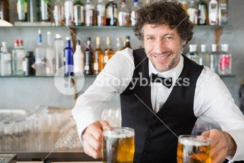 Waiter serving mug of beers