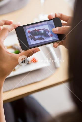 Woman taking photograph of meal