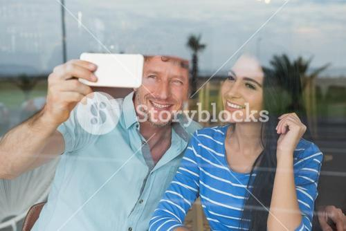Couple taking a selfie in cafeteria