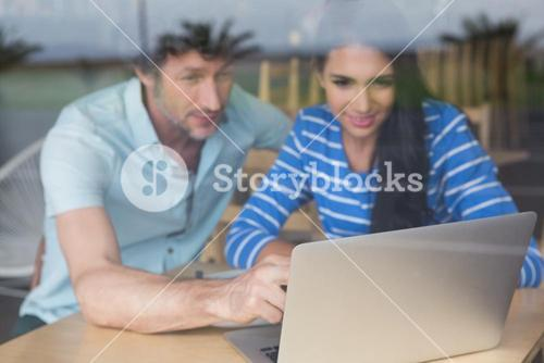Couple using laptop in cafeteria