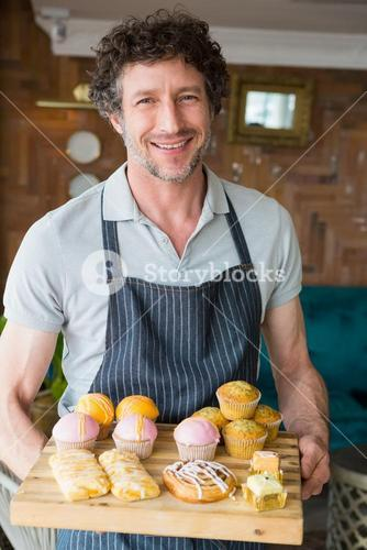 Waiter holding wooden tray with dessert