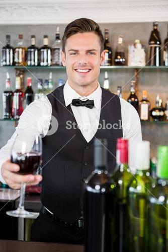 Waiter holding a glass of wine