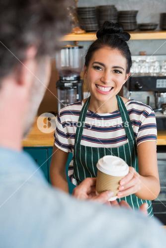 Waitress giving cup of coffee to customer